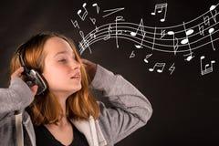 相当听到在耳机的音乐的女孩 免版税库存照片