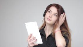 相当听到在采取照片片剂的无线耳机的音乐的女孩 影视素材