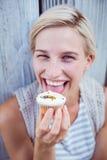 相当品尝杯形蛋糕的白肤金发的妇女 免版税库存照片
