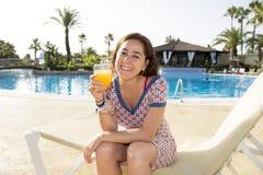 相当喝橙汁的可爱的拉丁妇女在水池 库存图片