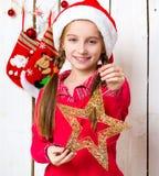 相当圣诞老人帽子的小女孩有星玩具的在手上 库存照片