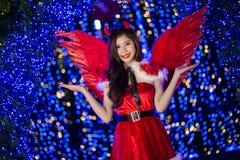 相当圣诞老人服装的亚裔女孩与夜ligh的圣诞节的 图库摄影