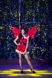 相当圣诞老人服装的亚裔女孩与夜ligh的圣诞节的 免版税库存图片