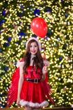 相当圣诞老人服装的亚裔女孩与夜ligh的圣诞节的 免版税图库摄影