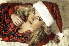 相当圣诞节红色长袍&圣诞老人帽子的白肤金发的女孩 免版税库存照片