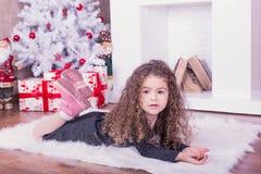 相当在一个壁炉附近的甜小女孩画象在圣诞节 库存图片