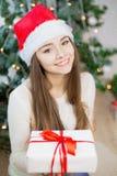 相当在圣诞老人帽子微笑和拿着当前近的圣诞树的女孩 背景Bokeh 库存照片
