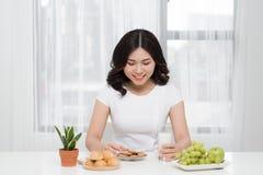 相当在家吃鲜美曲奇饼的年轻亚裔妇女 免版税库存图片