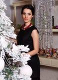 相当在家装饰圣诞树的端庄的妇女 免版税库存图片