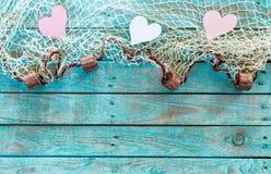 相当在捕鱼网的桃红色和白色心脏 库存照片