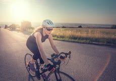 相当在日落的年轻适合妇女骑马自行车 免版税库存照片
