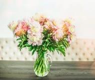 相当在玻璃花瓶的白色桃红色牡丹花束在桌,花卉家庭室内设计上 免版税库存图片