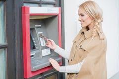 相当在ATM的白肤金发的妇女图画金钱 免版税库存图片