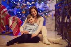 相当坐与她圣诞老人帽子的愉快的儿子的年轻母亲 免版税库存图片