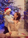 相当坐与她圣诞老人帽子的愉快的儿子的年轻母亲 免版税图库摄影