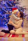 相当坐与她圣诞老人帽子的愉快的儿子的年轻母亲 库存照片