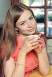 相当坐在与一杯咖啡的咖啡馆的少妇 免版税库存照片