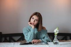 相当坐在咖啡馆和读杂志的小姐 免版税库存照片