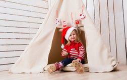相当坐在圆锥形小屋附近的红色帽子的小女孩 免版税库存照片