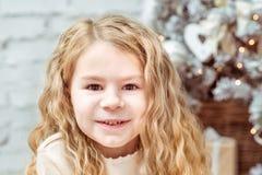 相当坐在圣诞树下的白肤金发的小女孩 库存图片