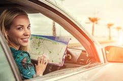 相当坐在有路线图的汽车的少妇 免版税库存图片