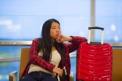 相当坐在机场有手提箱拿着护照和登舱牌的手提行李的登机口的亚裔韩国旅游妇女 库存图片
