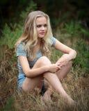 相当坐在草的白肤金发的少年 免版税图库摄影