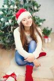 相当女孩在圣诞老人帽子在圣诞树附近坐并且微笑,在红色袜子 免版税库存图片