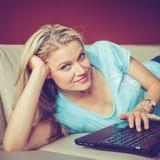 相当女孩在沙发和Chating说谎通过膝上型计算机 免版税图库摄影