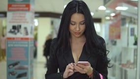 相当女孩在购物中心拿着购物袋并且使用一个巧妙的电话 股票视频