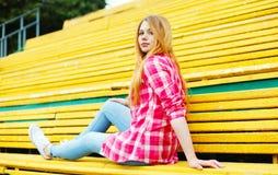 相当女孩坐的基于长凳在城市 库存照片