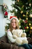 相当女孩拥抱玩具熊在圣诞前夕 库存照片
