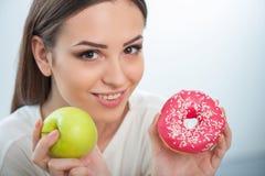 相当女孩用健康和不健康的食物 免版税图库摄影