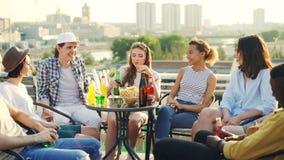相当女孩讲故事对她的朋友不同种族的小组在桌上坐屋顶用食物并且喝 股票视频