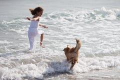 相当女孩运行与在海水的一条狗 库存图片