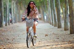 相当女孩骑马自行车和谈话在电话 免版税图库摄影