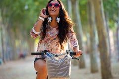 相当女孩骑马自行车和谈话在电话 免版税库存图片