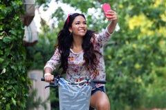 相当女孩骑马自行车和采取selfie 免版税库存照片