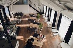 相当女工享受他们的工作 两名女实业家在咖啡馆,一坐看照相机 免版税库存照片