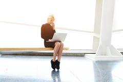 相当女性与在有的膝盖的网书手机交谈 库存照片