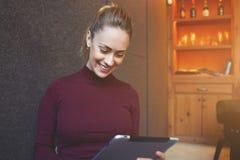相当女性与美好的微笑使用数字式片剂,当坐在现代咖啡馆酒吧内部时 免版税库存照片