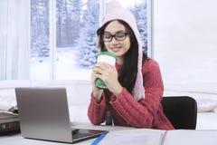 相当女性与膝上型计算机和热巧克力 免版税库存图片