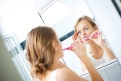 相当女性刷她的在镜子前面的牙 库存图片