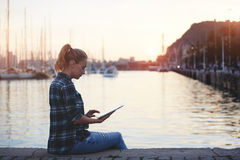 相当女性在数字式片剂的读书电子书,当放松户外在休闲时间时 库存照片