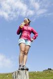 相当女性在树桩的远足者饮用水 免版税图库摄影