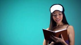 相当女性在睡衣看书在睡觉前,松弛上床时间仪式 库存照片