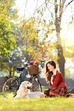 相当女性坐下与她的狗在公园 免版税库存图片
