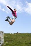 相当女性远足者从树桩跳 免版税库存照片