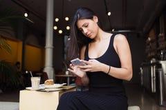 相当女性连接到在电话的无线,当休息在新鲜空气时的舒适咖啡店 库存照片