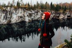 相当好女孩在卡累利阿享受从hilltopl的美好的湖视图和好天气 在岩石附近 免版税库存照片